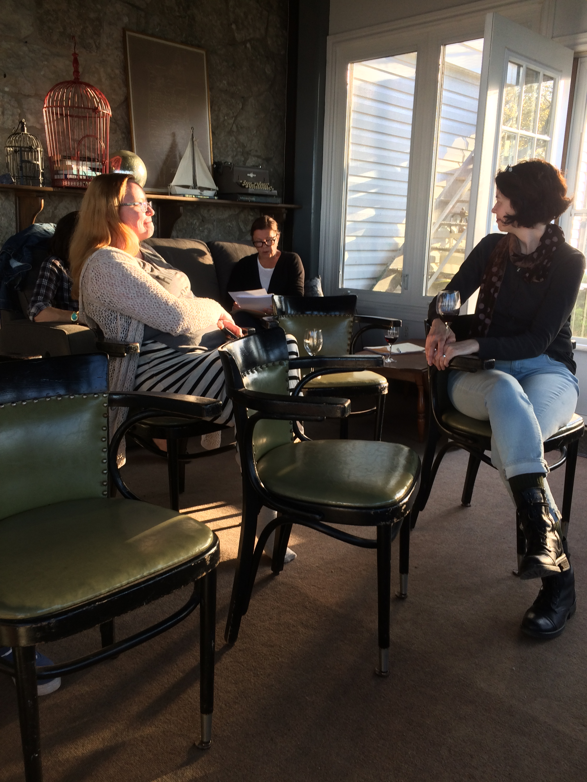 Writers Dawn Kresan & Alisa York listen to a reading from Diana Leszczynski at magic hour on Pelee Island