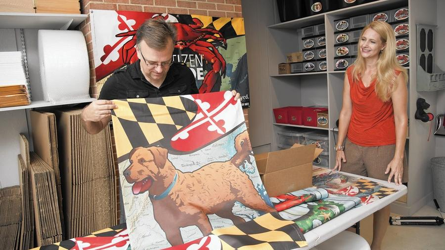 joe and eva barsin in THEIR STORAGE ROOM/SHIPPING ARE a, showing their maryland chessie hosue flag. --  PHOTO BY JOSH MCKERROW.