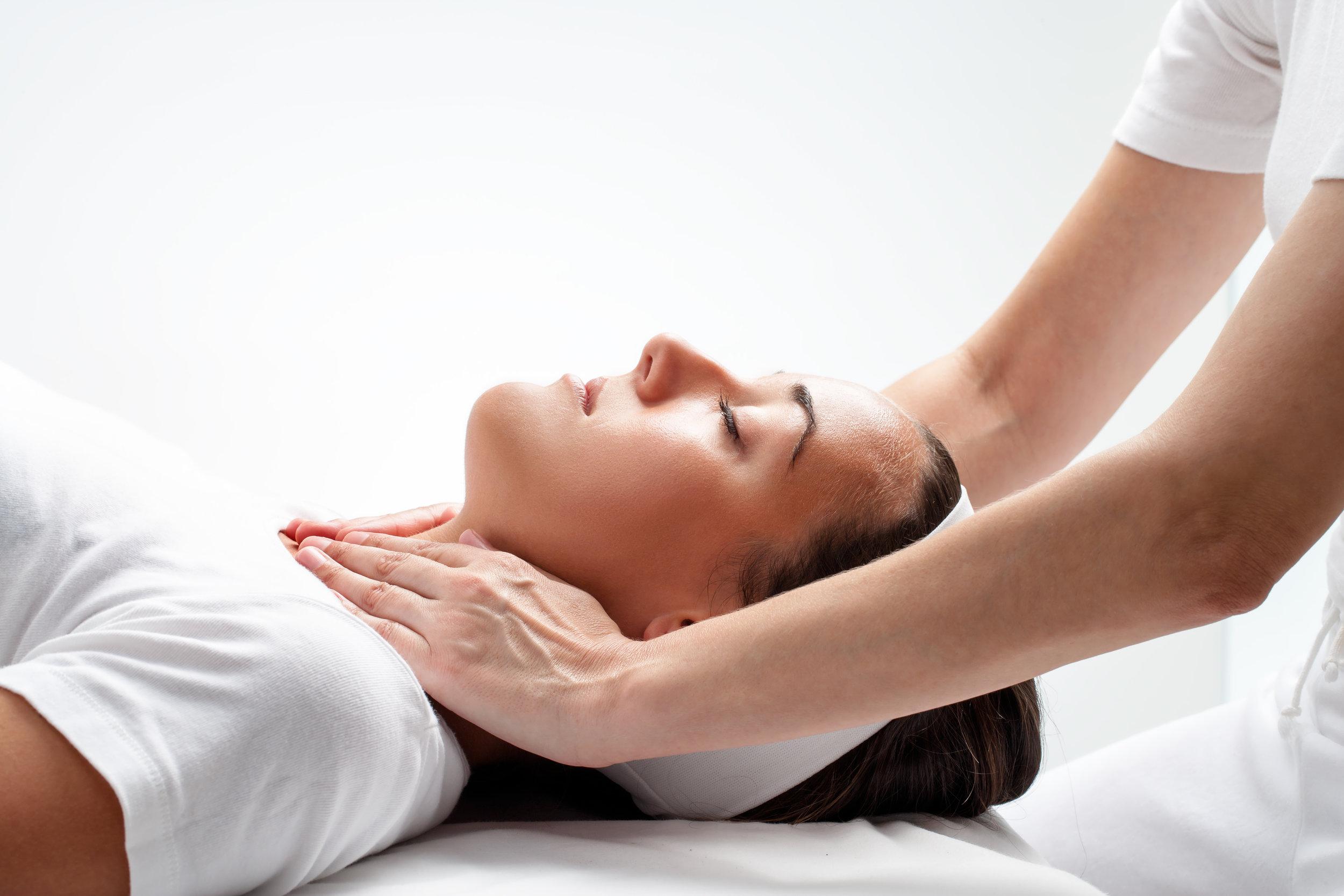 Therapist doing reiki on woman's neck.