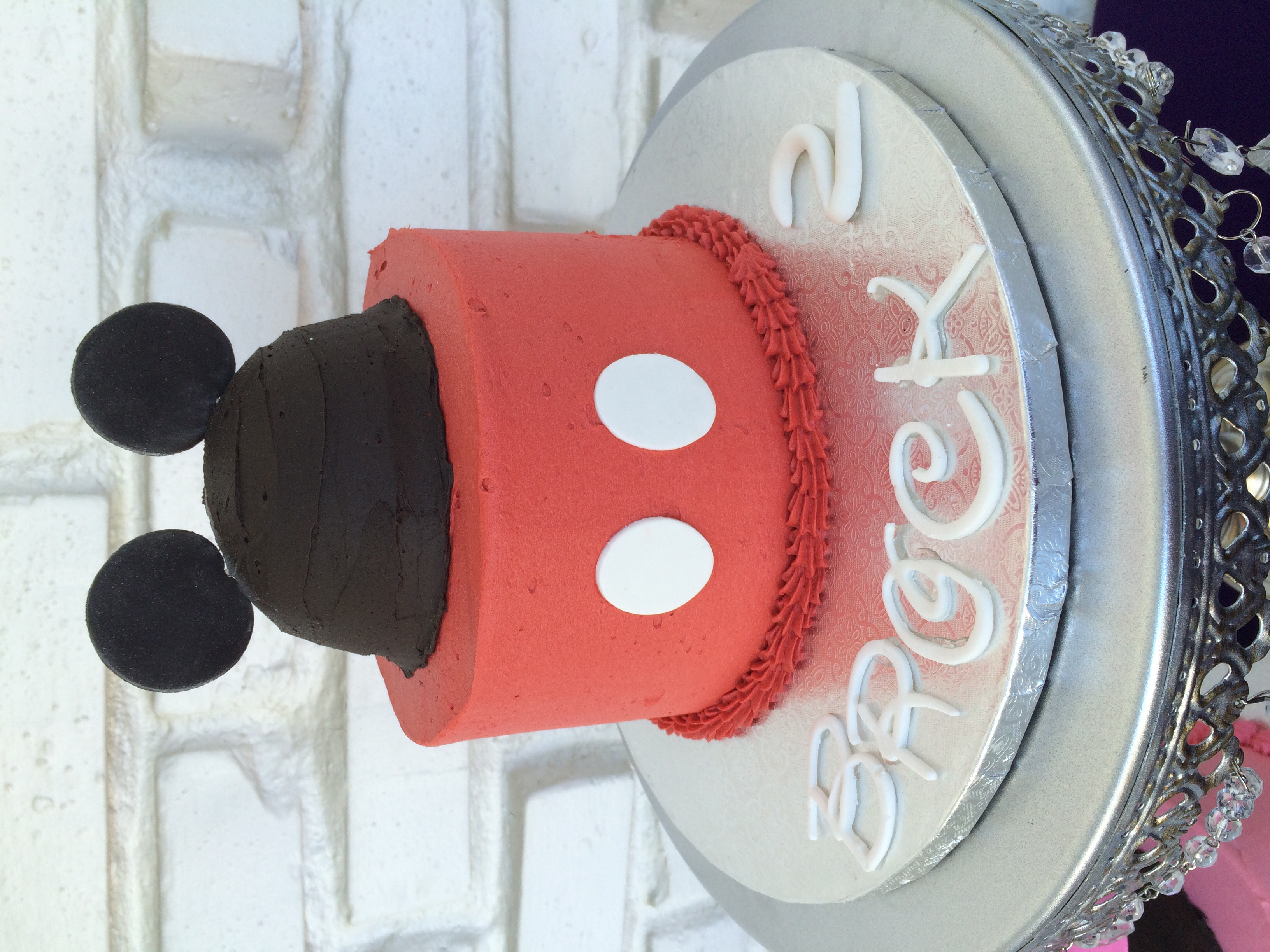 Chocolate cake filled with black cocoa buttercream and covered with vanilla buttercream and fondant accents