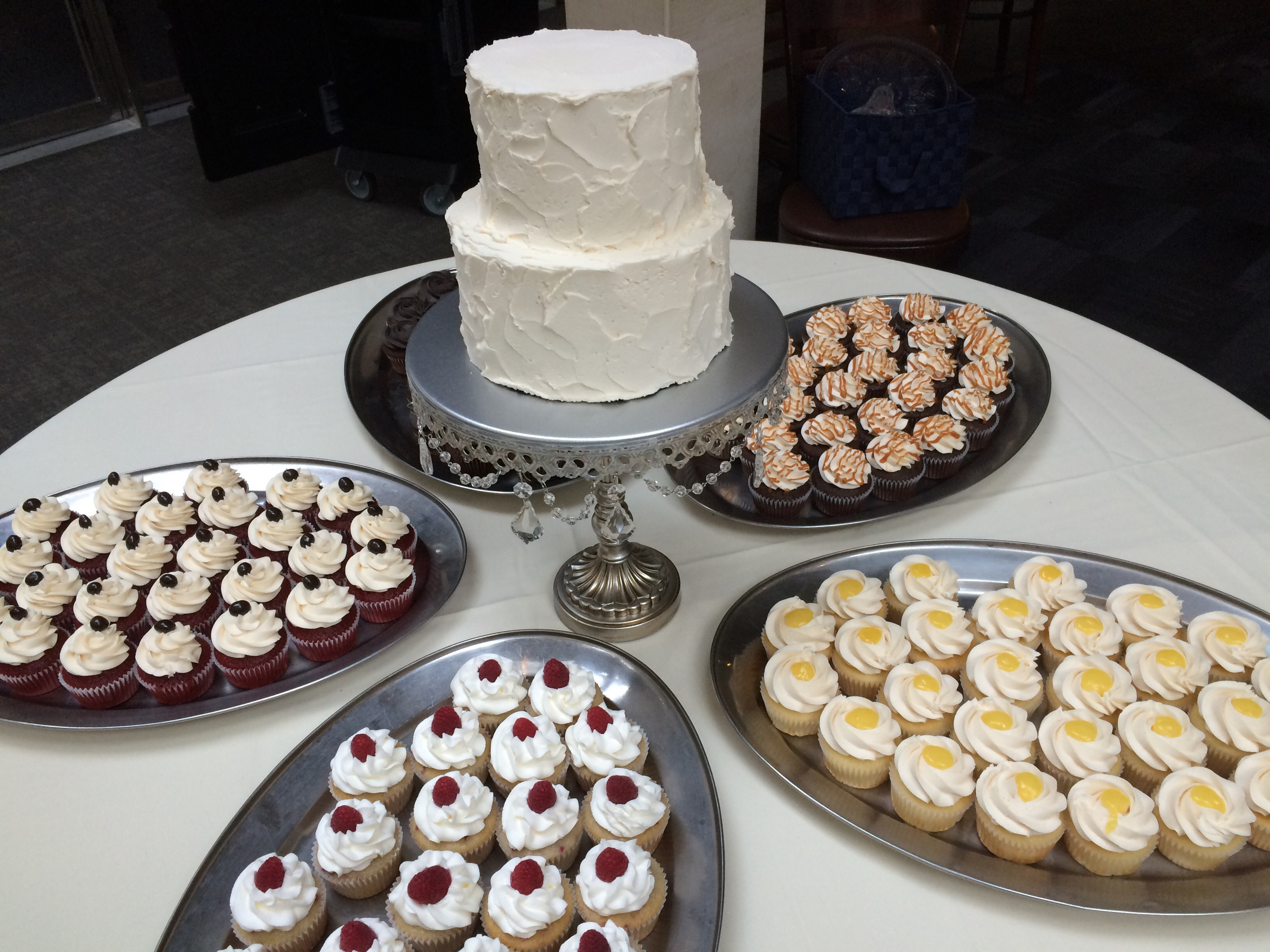 Wedding cakes, top tier is lemon and bottom tier is salted caramel, surrounded by various cupcake flavors