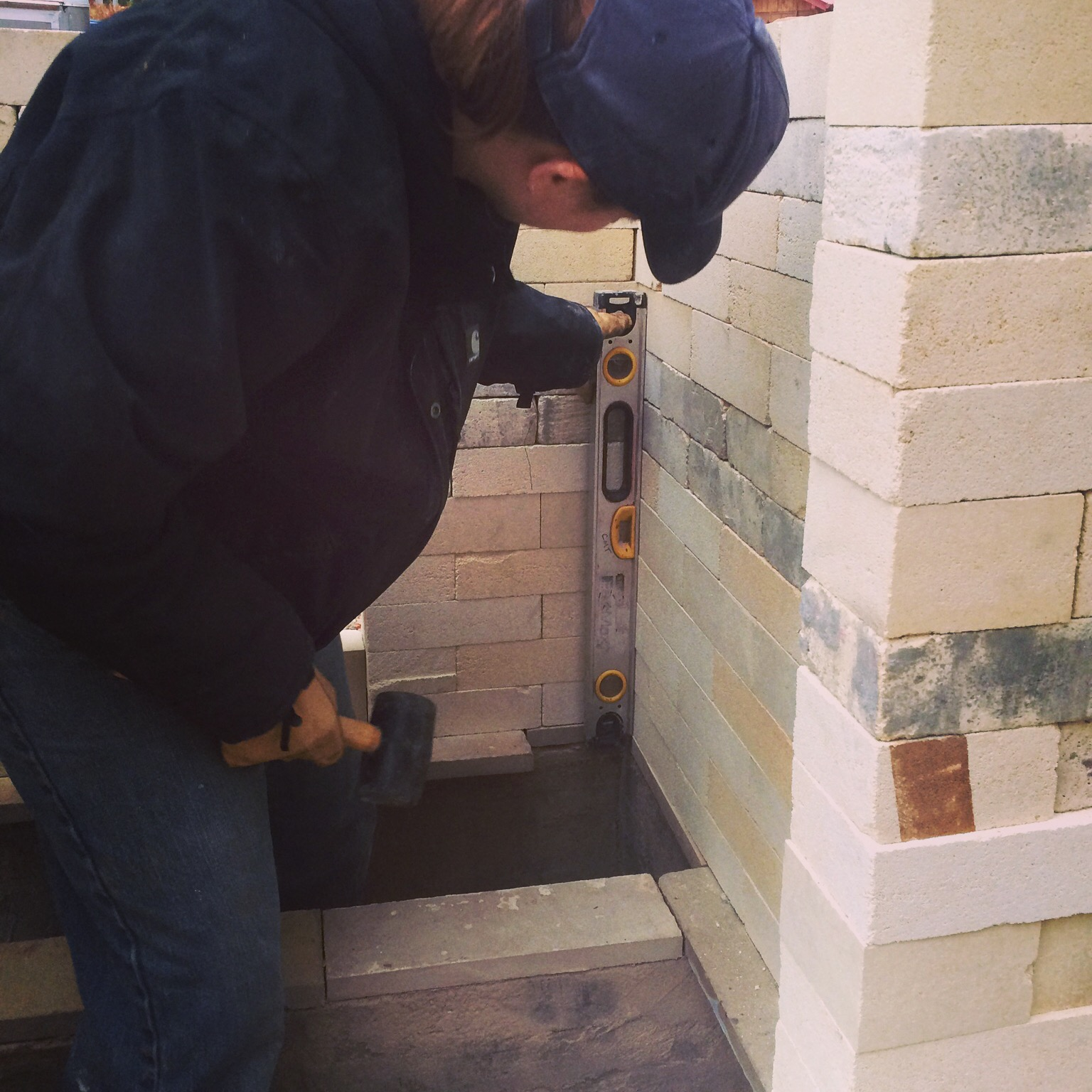As we lay the bricks out, we ensure that we have nice straight walls by leveling them, from the inside and tapping
