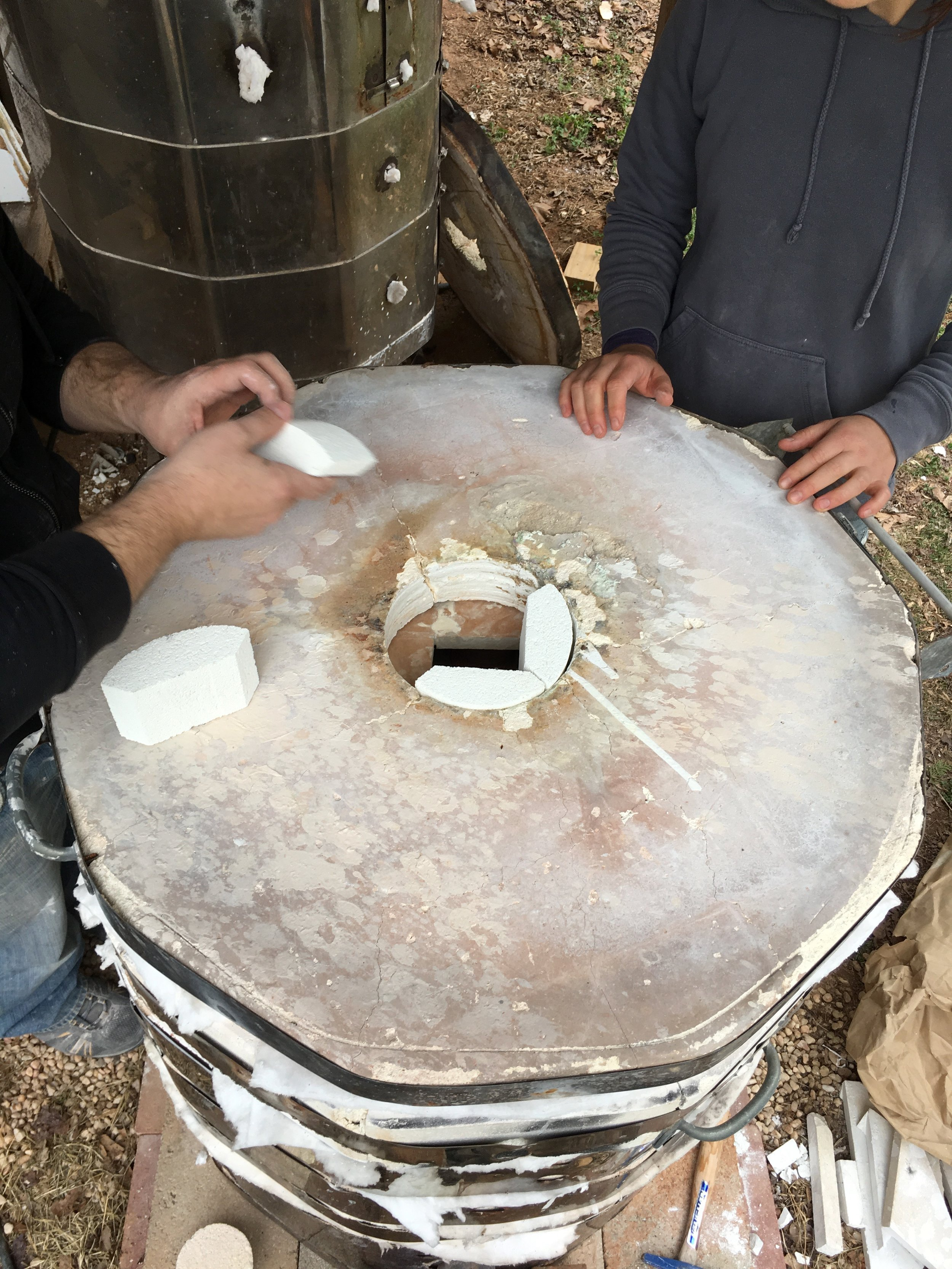 """To close the kiln and protect the soft brick, Jarad custom cut shelves that are placed between the top ring and the lid of the kiln. He puts in """"chips"""", which are made of high alumina soft brick, around the opening at the top of the kiln. A layer of insulating kaowool is put between each of these layers and wherever else there may be a small opening."""