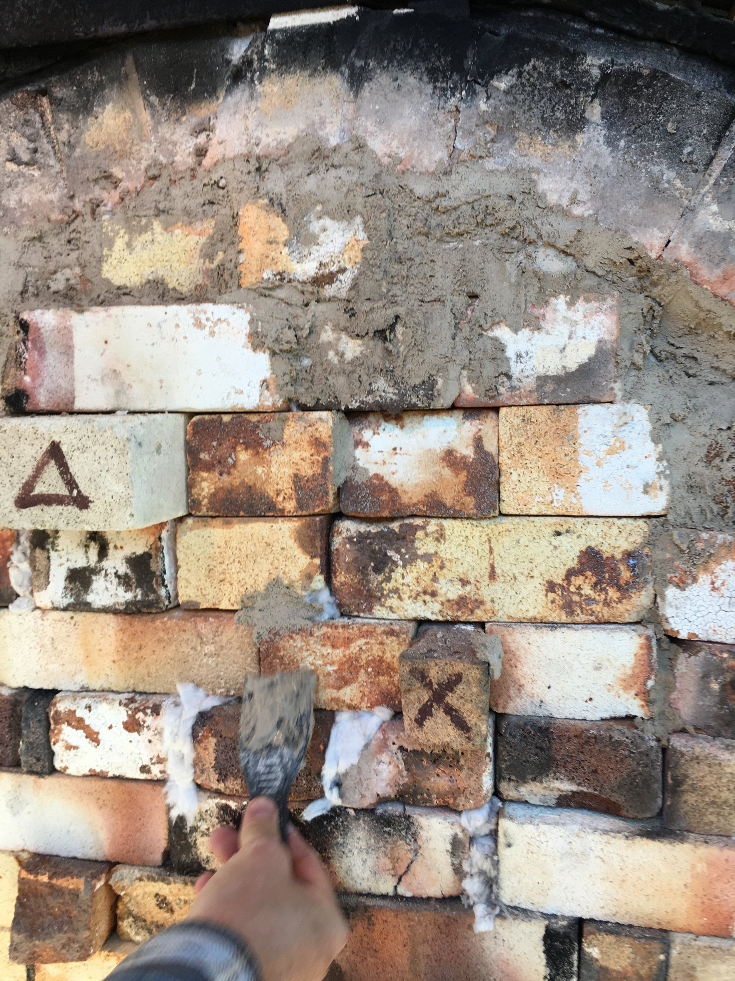 """Muddin'"" the door--we fill any cracks with a clay slurry to ensure heat retention. Some of the door bricks are marked--the triangle on the brick lets us know a cone pack is behind it, and X marks the salt spot!"