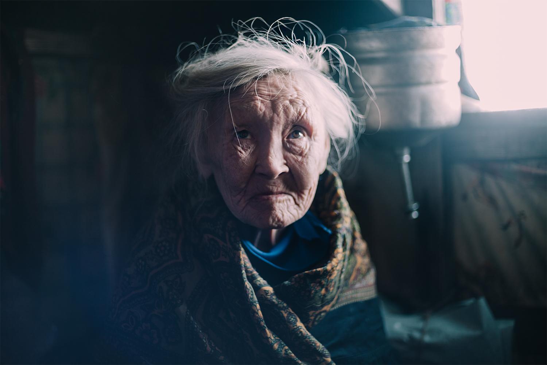 Veterana mujer de la etnia Nenet mira fijamente a cámara en el interior de su Balok. Posiblemente sea la primera vez que ve un forastero venido de europa.