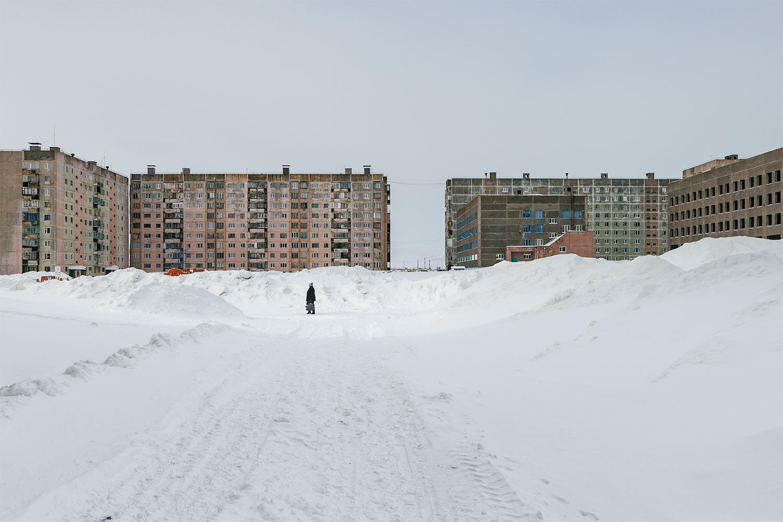Periferia de Norilsk, barrio de Oganer. Los barrios durante el invierno están inmersos en nieve que se descongela en verano causando algunas pequeñas arriadas. La actividad humana es mínima, la fotografía habitual son personas deambulado en medio de un escenario post-apocalíptico.