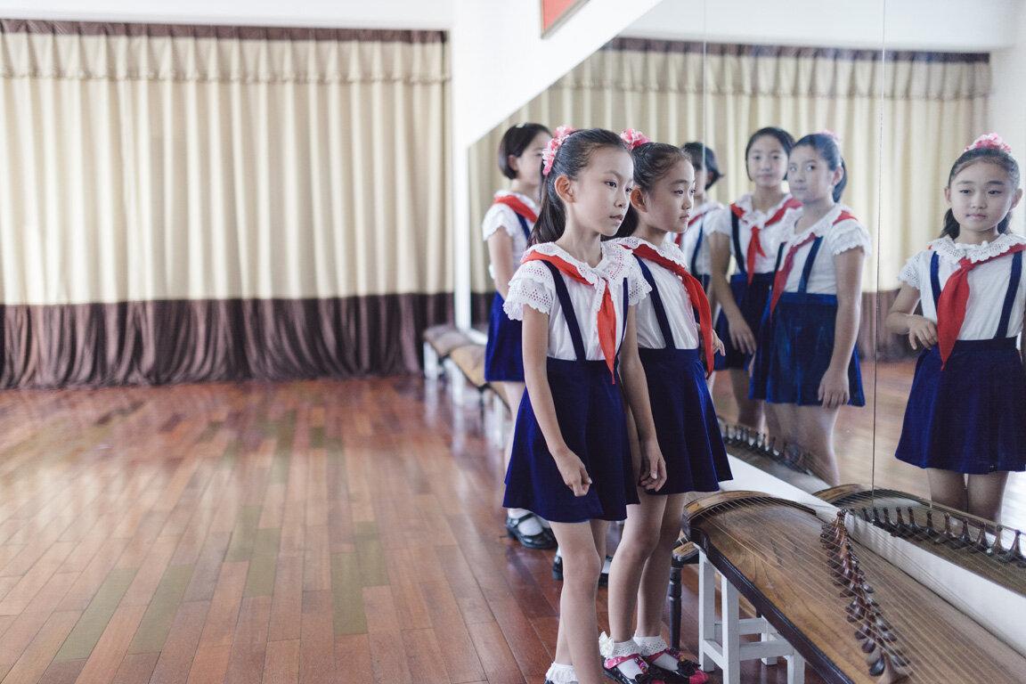 Niñas ensayan observándose en el espejo en el palacio infantil de la música en la capital de Korea del Norte, Pionyang.