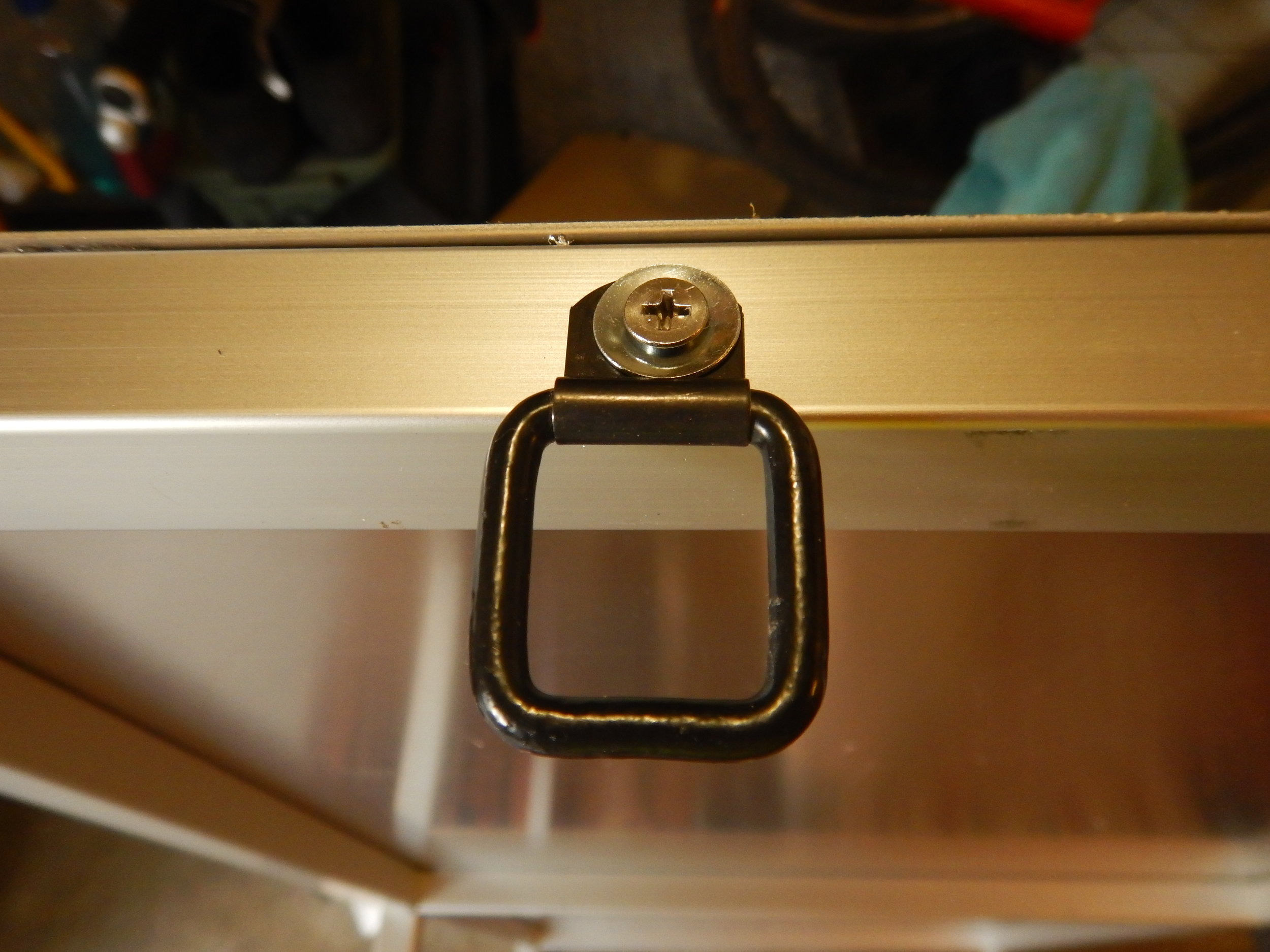 single-eyelet D-ring bolted to the shelf frame rail.