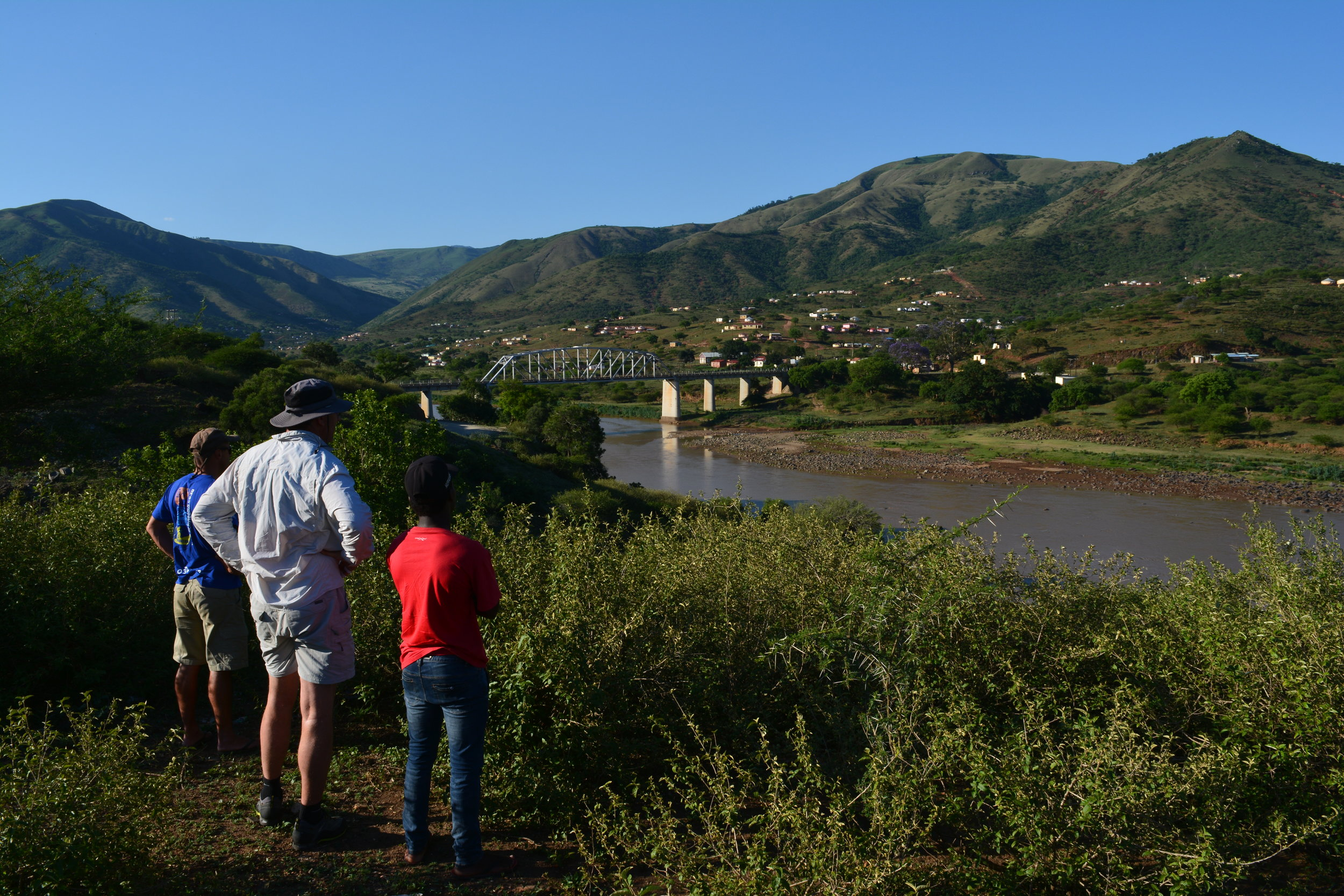 Gustav Greffrath, Hugh du Preez, and Godfrey Tshumah ponder the water level of the Tugela River, looking down at Jameson's Drift.