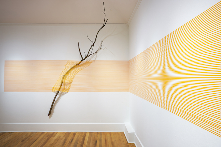 """Orange  Stick  II  (41.8441 ° N,  71.4382 ° W)   2017  masking  tape  and  found  sticks  144""""  x  432""""  x  16""""  Image courtesy of Providence College Galleries (PC-G)"""