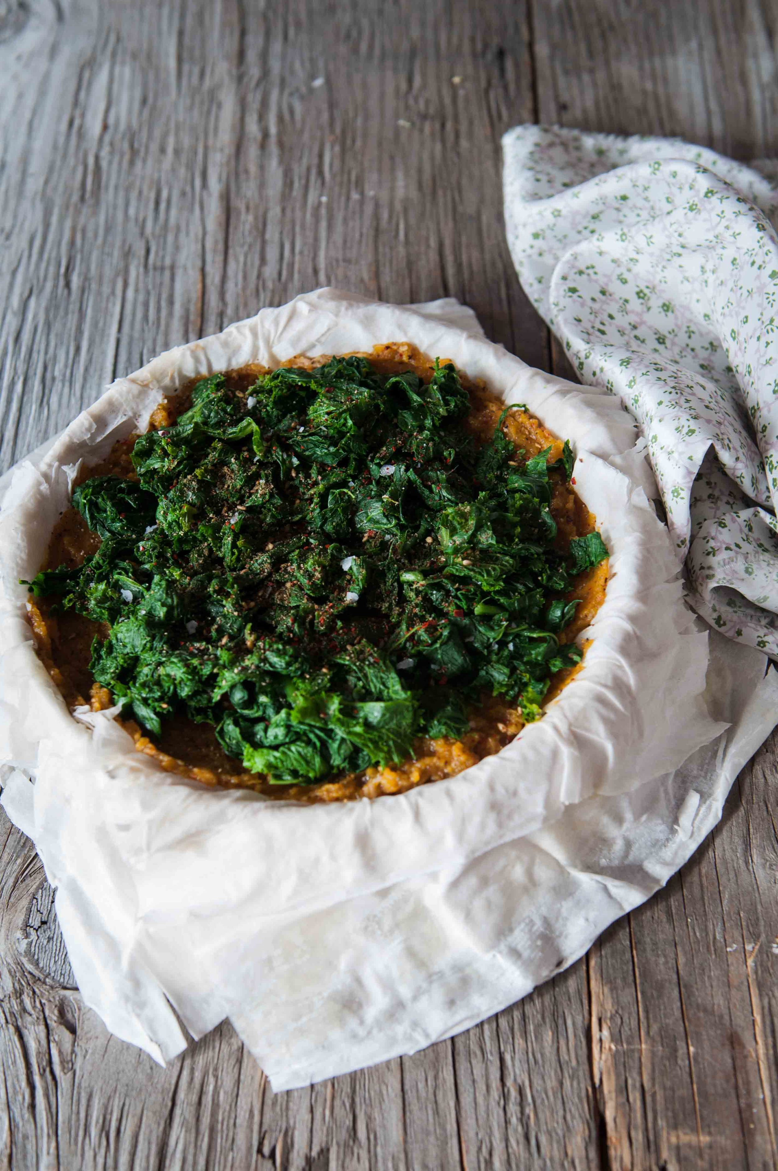 Filled pie with pumpkin puree, hummus and steamed mustard greens.