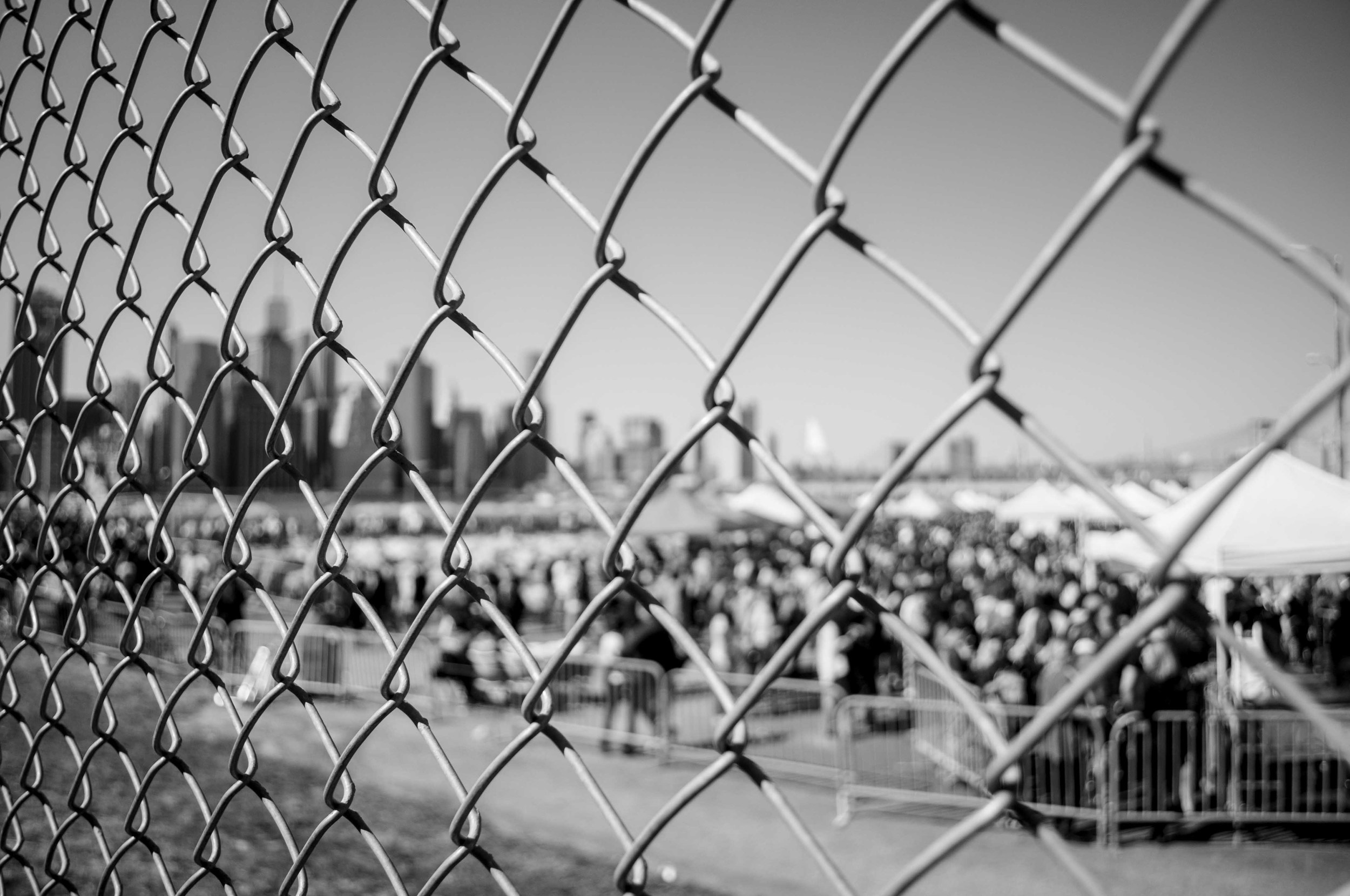 Looking through the fence into the outdoor market of Smorgasburg where the people milled, tasted, laughed and chatted.