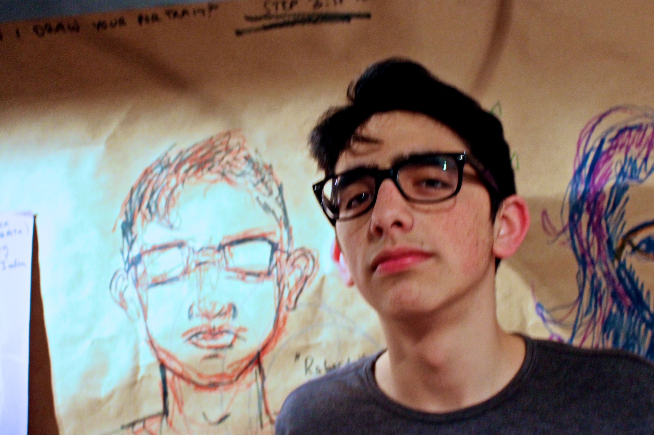 Roberto Rochin '17 poses next to a portrait drawn by Lilly Rosner '14