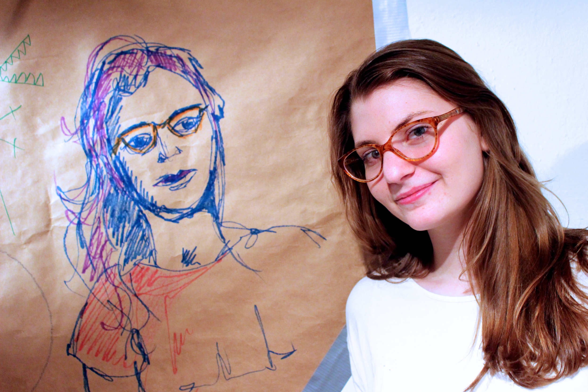 Lilly Rosner '14 poses next to a portrait done by Lili Boisrond '17