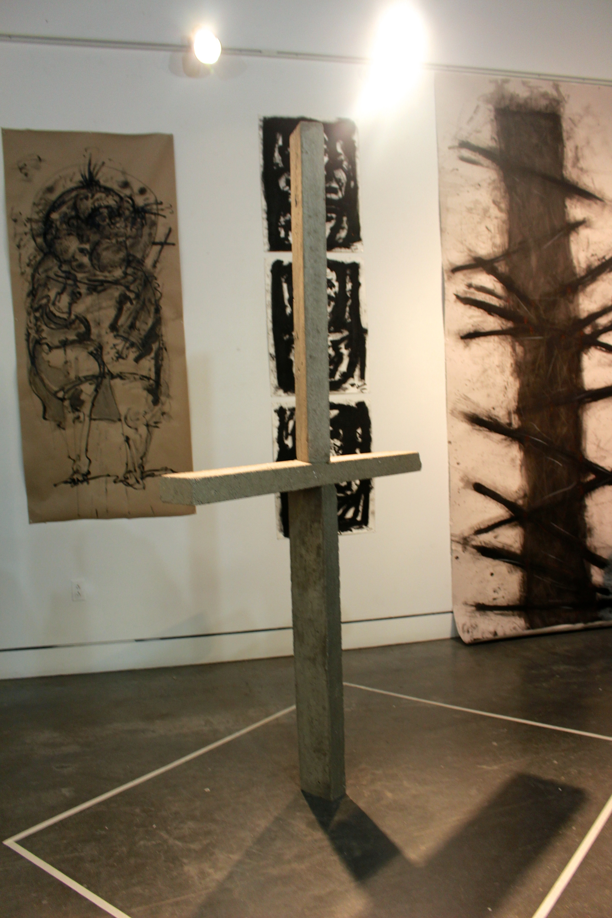 A cross constructed by Alan Medina '14 stands in front of the religiously inspired works of Alexis de Chaunac '14