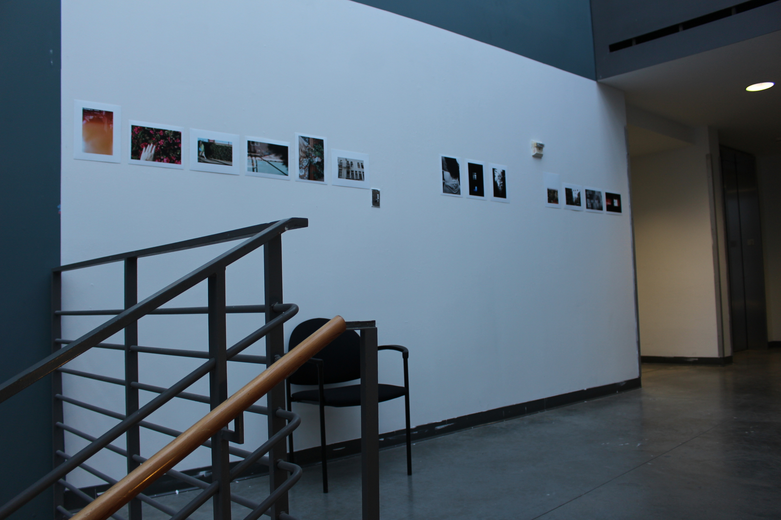 Photographs by Emily Alben hung on the floor above the Atrium