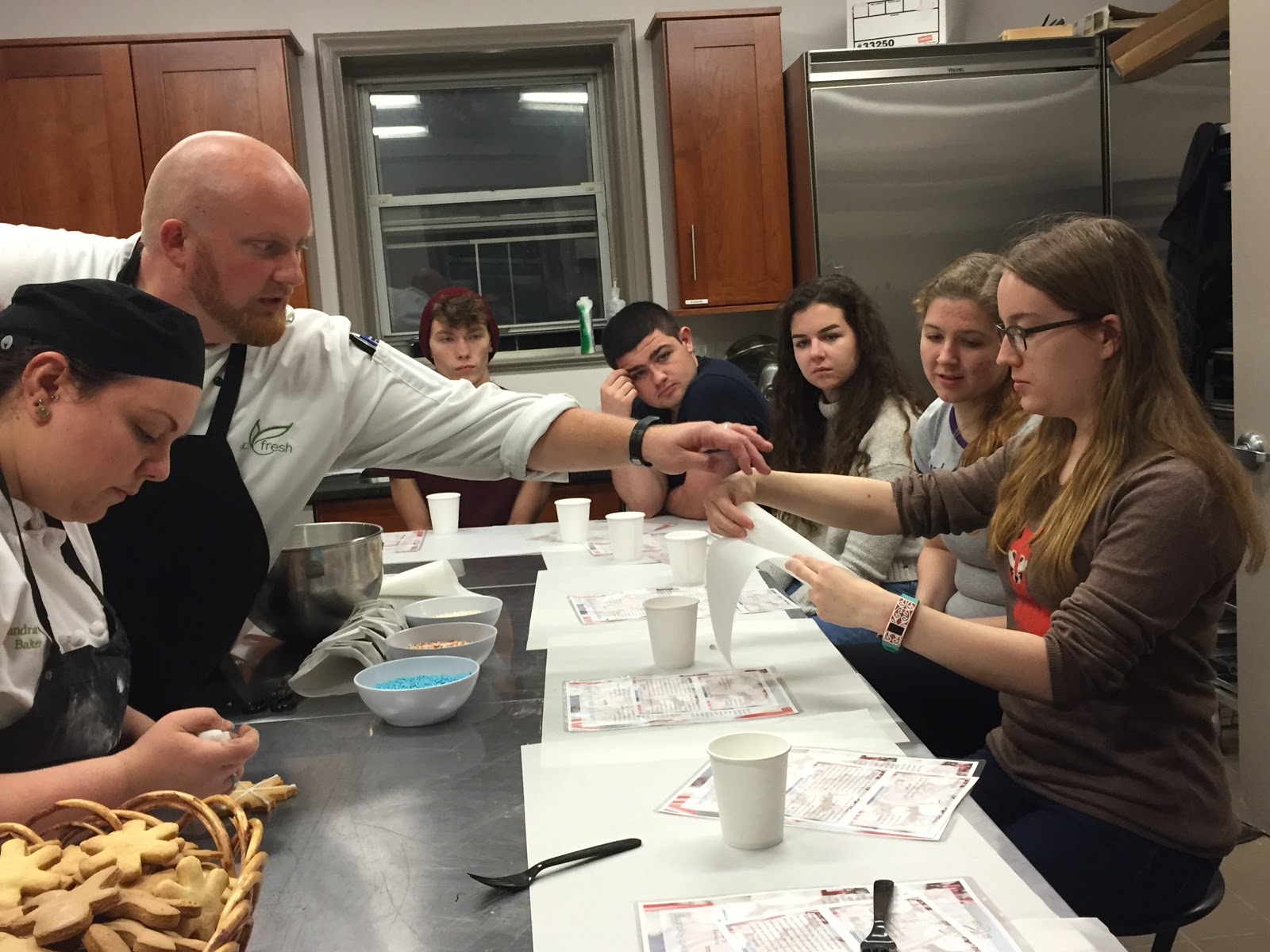 SLC Fresh Executive Chef Jordan Luchini teaches Sarah Sargent ('17) how to make a parchment pastry cone. Photo credit: Victoria Mycue '20