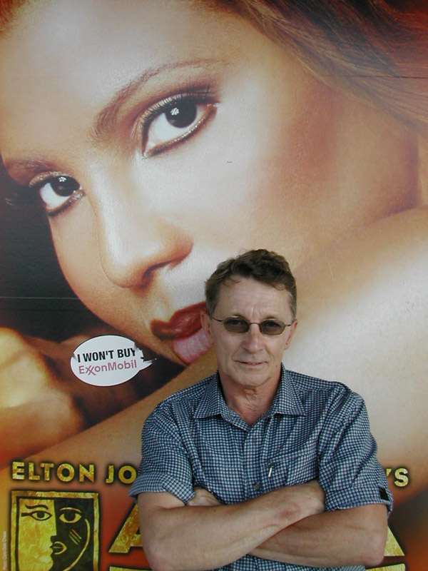 Jerry Schrader in front of a giant poster of an attractive woman, whispering that she won't buy Exxon/Mobil in his ear.