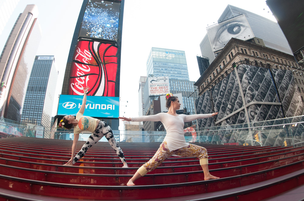 Meryl & Meredith perform Trikonasana (triangle pose) and Virabadrasana II (warrior pose) on the famous red steps in Times Square