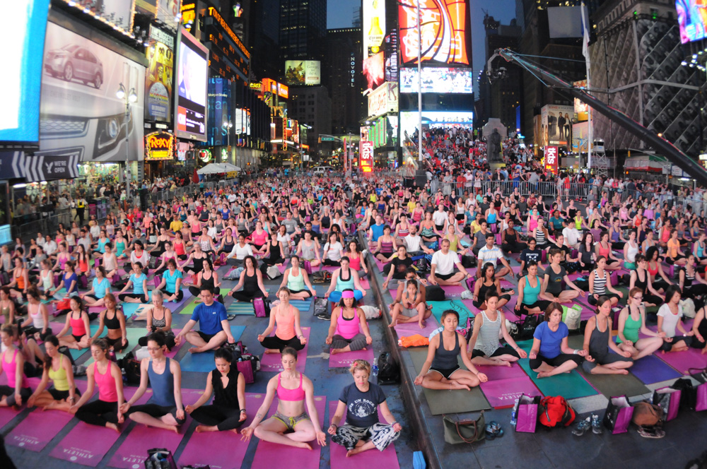 An ocean of yogis meditating after sunset at Solstice in Times Square