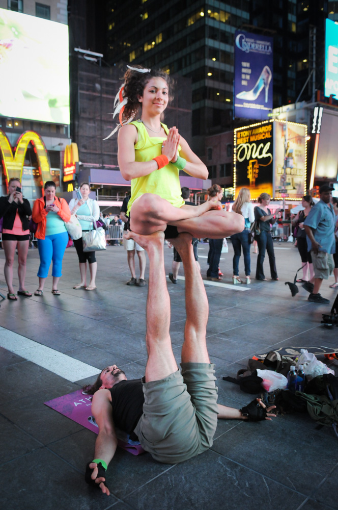 Acroyoga after dark in Times Square with Elana Jaroff performing lotus on the feet of her base