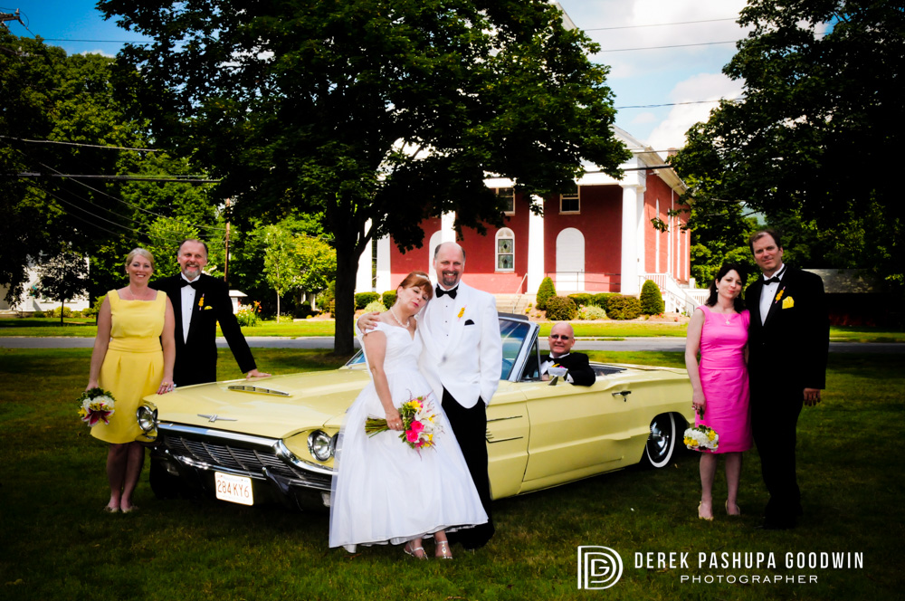 A formal portrait of the bride and groom with wedding party and 1964 Thunderbird Convertible