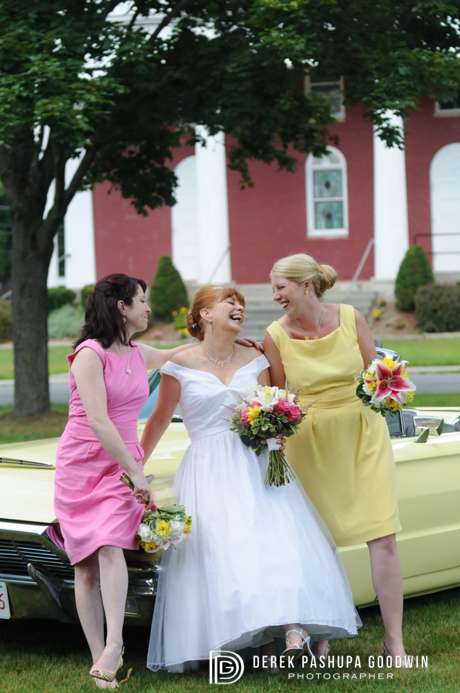 The bride laughing with her bridesmaids on antique car