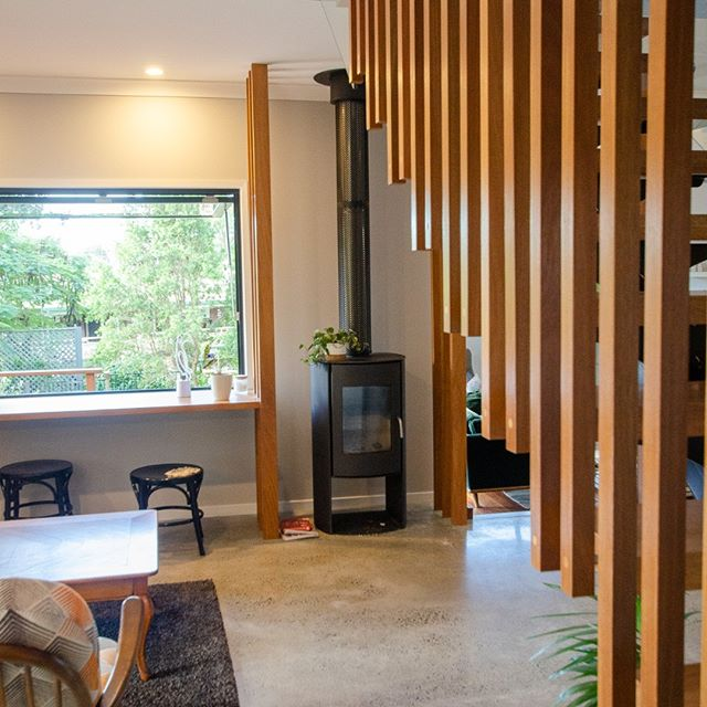 The stair balustrade slowly revealing the fireplace. An intimate interstitial zone between the sunken lounge and the bar seating with large north facing awning window overlooking the courtyard. The many functions of a small house to suite changing seasons and different user modes. EL house. #queenslandarchitecture #goldcoastarchitecture #resonanceda #subtropicaldesign #fireplace #thermalmass #timberscreen