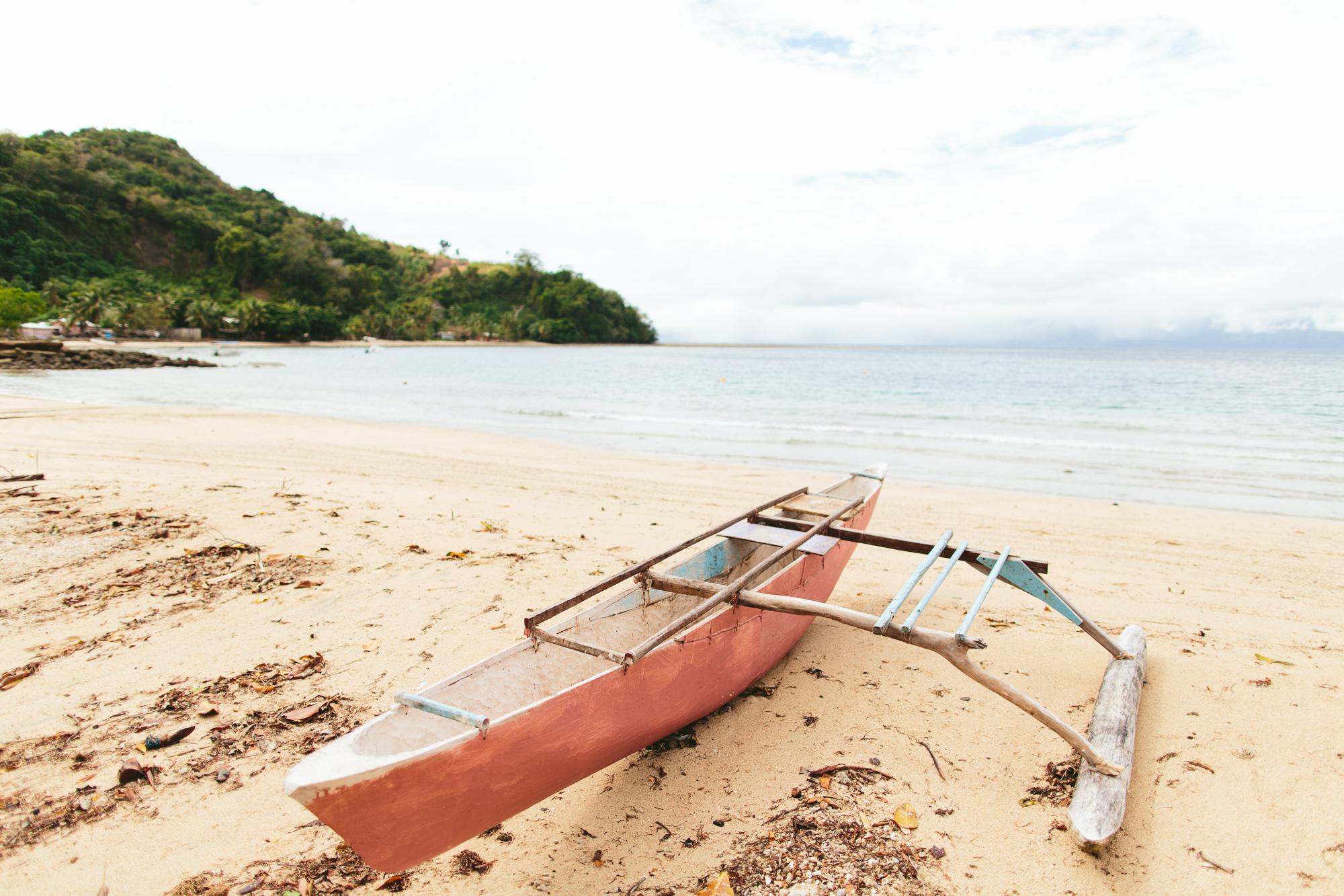 Dugout canoe on Kioa Island beach - The Remote Resort Fiji Islands