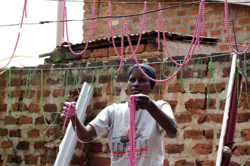 Evelyn hangs strings of freshly painted beads to dry in her backyard.