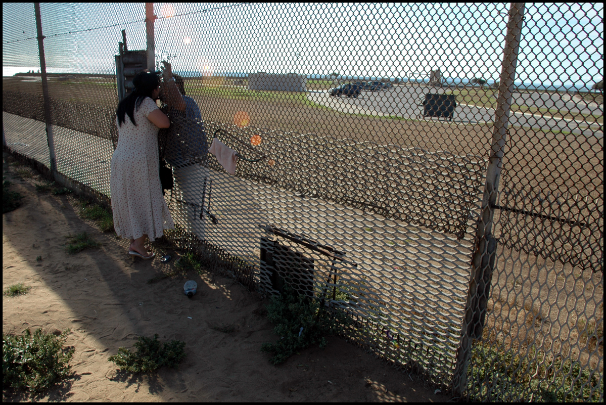 29 Jul 2006, Tijuana, Mexico --- A Mexican woman, on the Mexican side of the border fence, and a man on the American side, unable to cross the border to be with each other