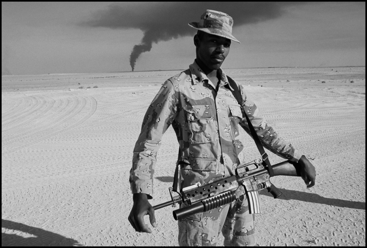 February 1991, Kuwait --- February 1991: A US soldier stands in the desert as a Kuwaiti oil rig burns out of control in the distance.