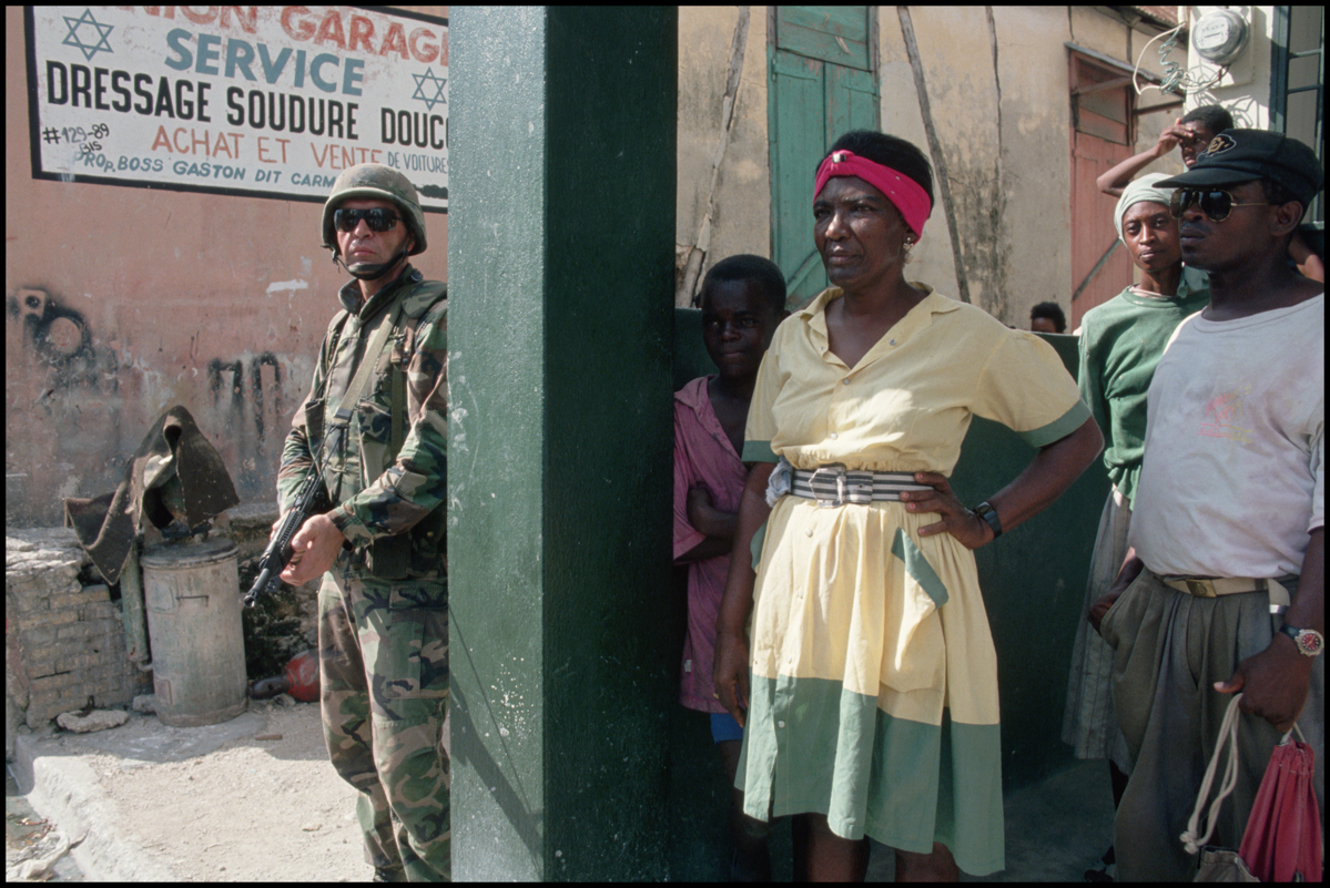 September 1994, Port-au-Prince, Haiti --- Residents of Port-au-Prince stand near an American soldier.