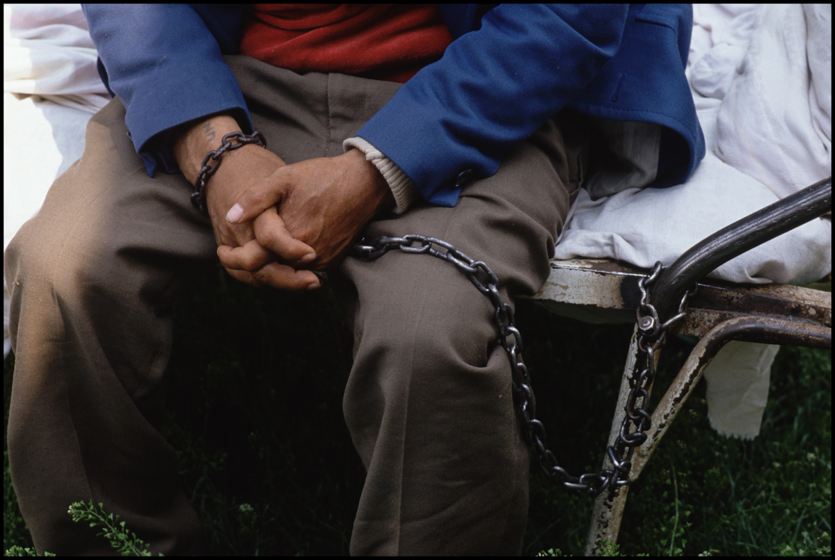 16 May 1990, Gradinari, Romania --- A patient at the mental hospital in Gradinar, Romania sits chained to a cot.