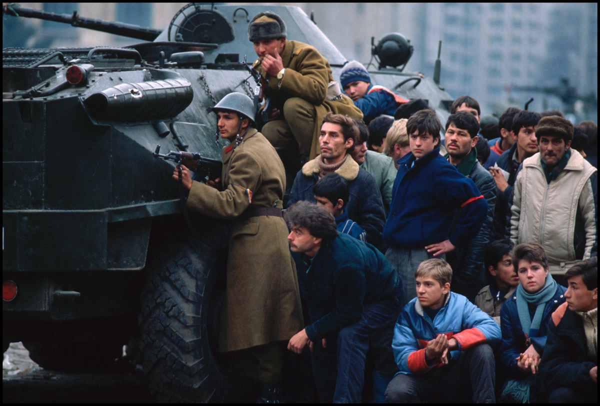 1989, Bucharest, Romania --- During the 1989 revolution, Romanian soldiers and civilians take cover behind a tank in Bucharest's Palace Square.