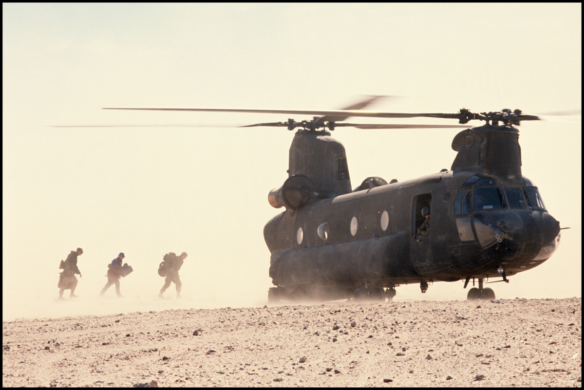 Three U.S. soldiers walk towards a CH-46 Chinook transport helicopter near an American base in Saudi Arabia. The allies are preparing to liberate the Iraqi-occupied Kuwait.