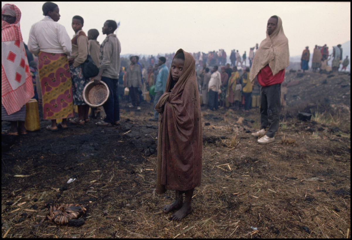 28 Jul 1994, Goma, Democratic Republic of the Congo --- A young Rwandan Hutu refugee stands with other refugees. They have fled the civil war in Rwanda and suffer from a cholera epidemic.