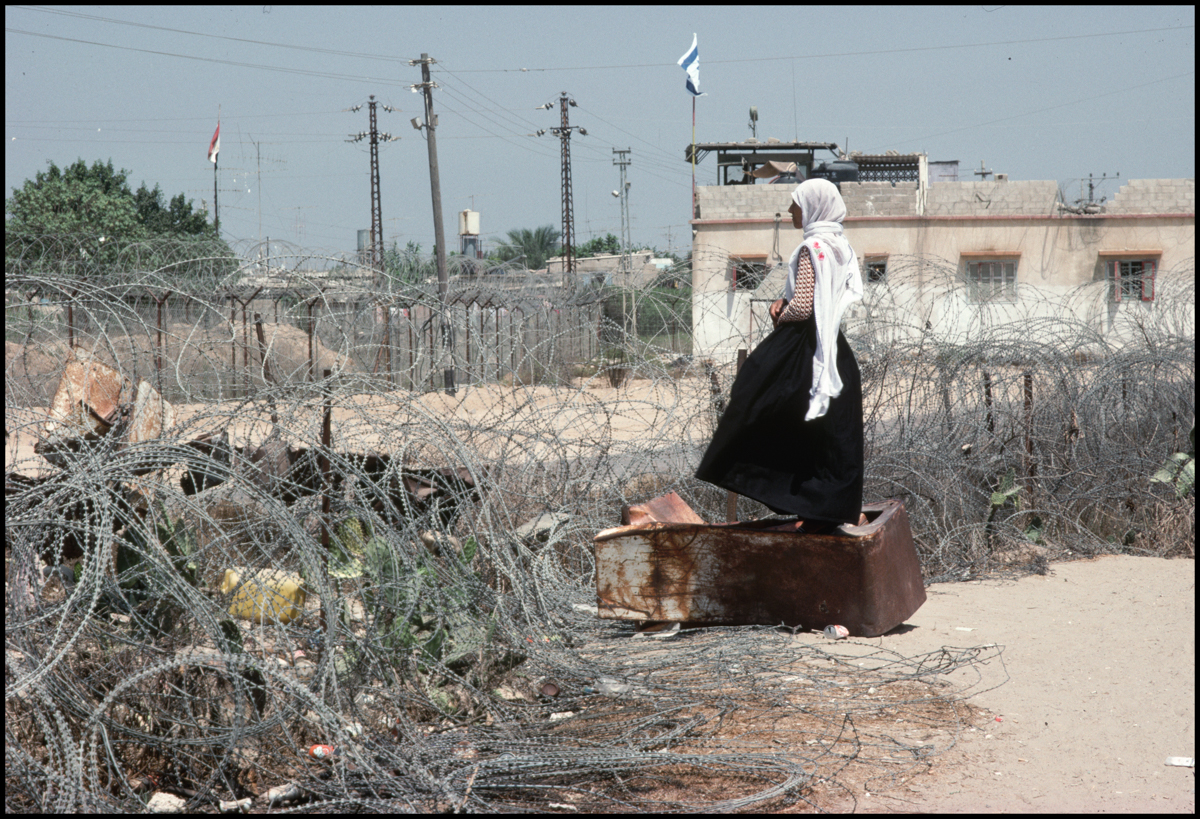 July 1988, Gaza, Gaza Strip --- A Palestinian refugee in a refugee camp looks out over barbed wire into another camp across the border between Gaza and Egypt.