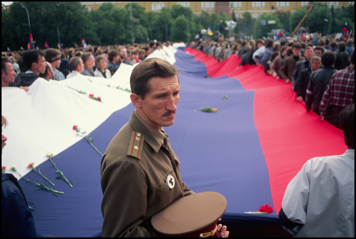 22 Aug 1991, Moscow, Russia --- A huge Russian flag is unfurled by mourners at a mass funeral for victims of the failed coup attempt.
