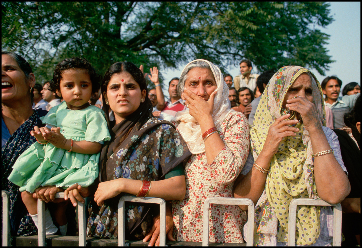 03 Nov 1984, New Delhi, India --- A group of women and a girl, mourners watching the funeral procession of Indira Gandhi.