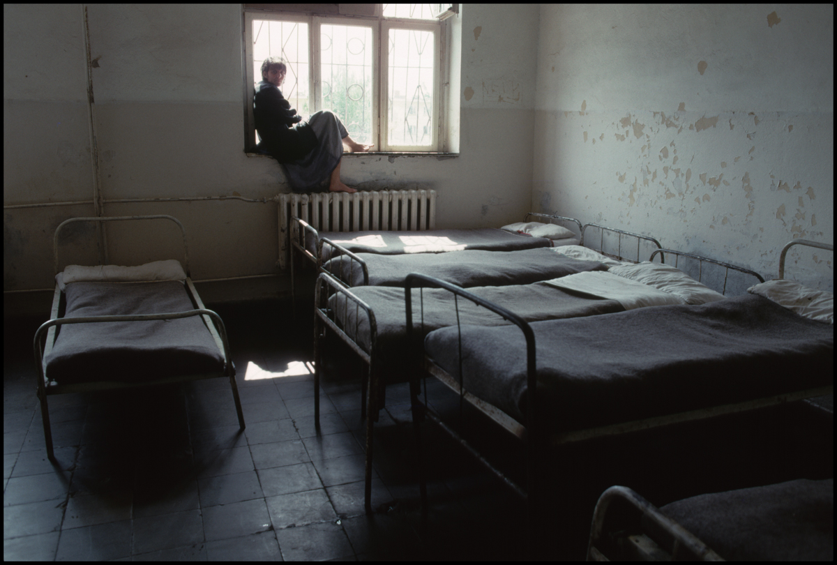 31 Mar 1992, Elbasan, Albania --- An Albanian man sits on the windowsill of a dingy room with neatly made beds in the Elbasan Psychiatric Hospital.