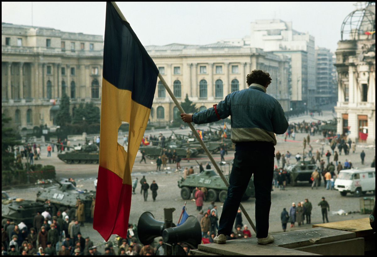 1989, Bucharest, Romania --- A man holds a Romanian flag with the Communist symbol torn from its center on a balcony overlooking the tanks, soldiers, and citizens filling Palace Square