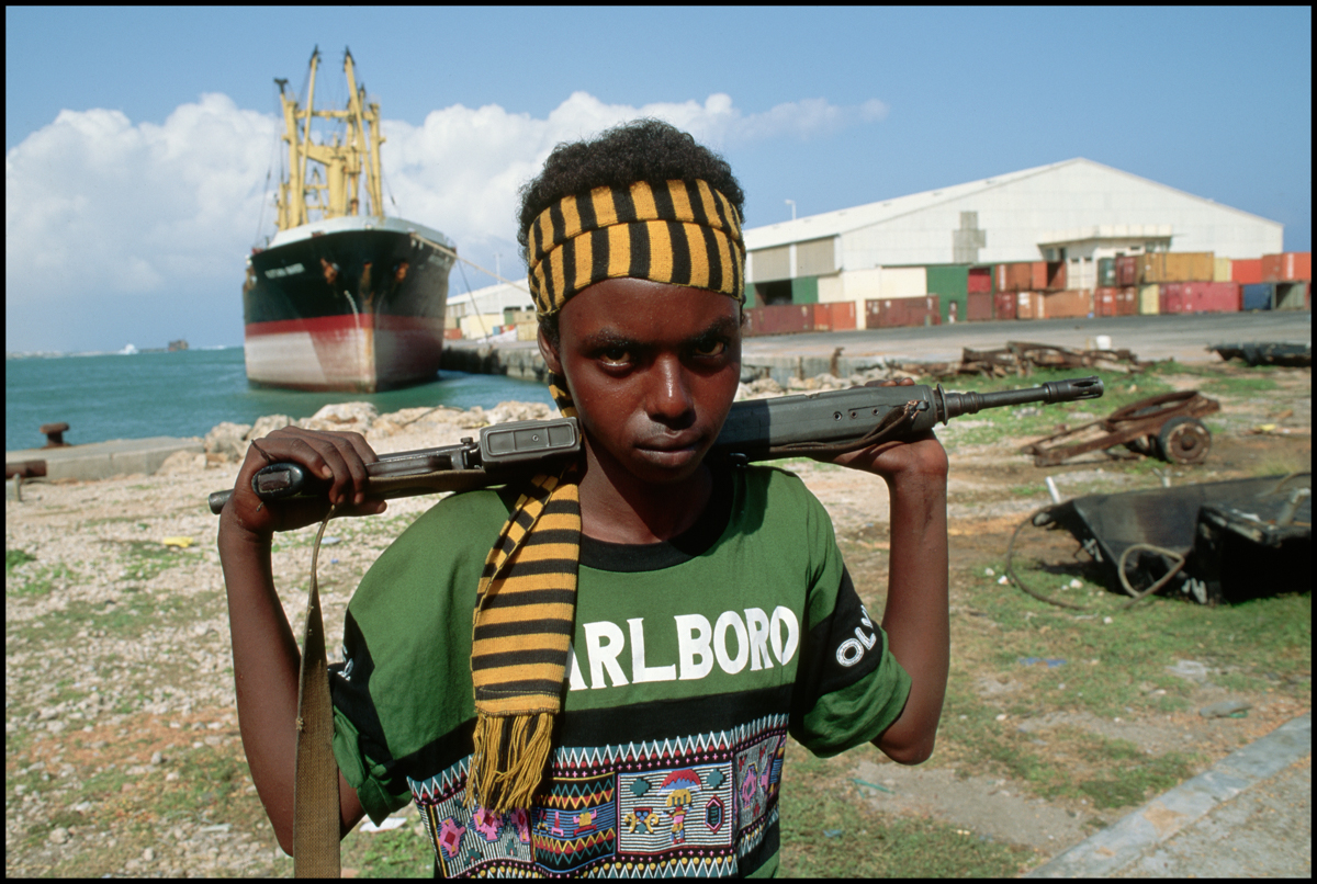 02 Sep 1992, Mogadishu, Somalia --- A Somali militiaman, part of a factional militia group fighting in the civil war, casually holds his gun while guarding the port where all food aid enters the city
