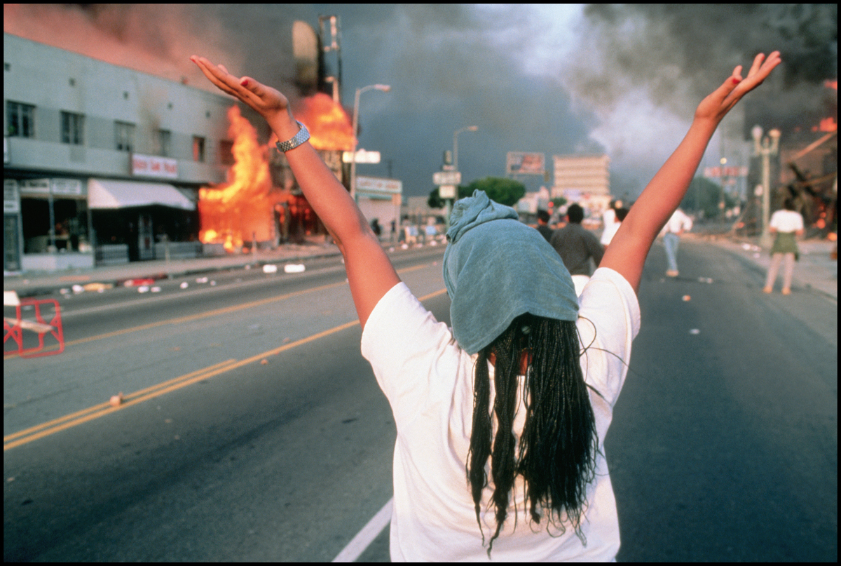 30 Apr 1992, Los Angeles, California, USA --- An African American woman from Los Angeles raises her hands high, taking in the burning buildings and looting all around her during the LA riots of 1992.
