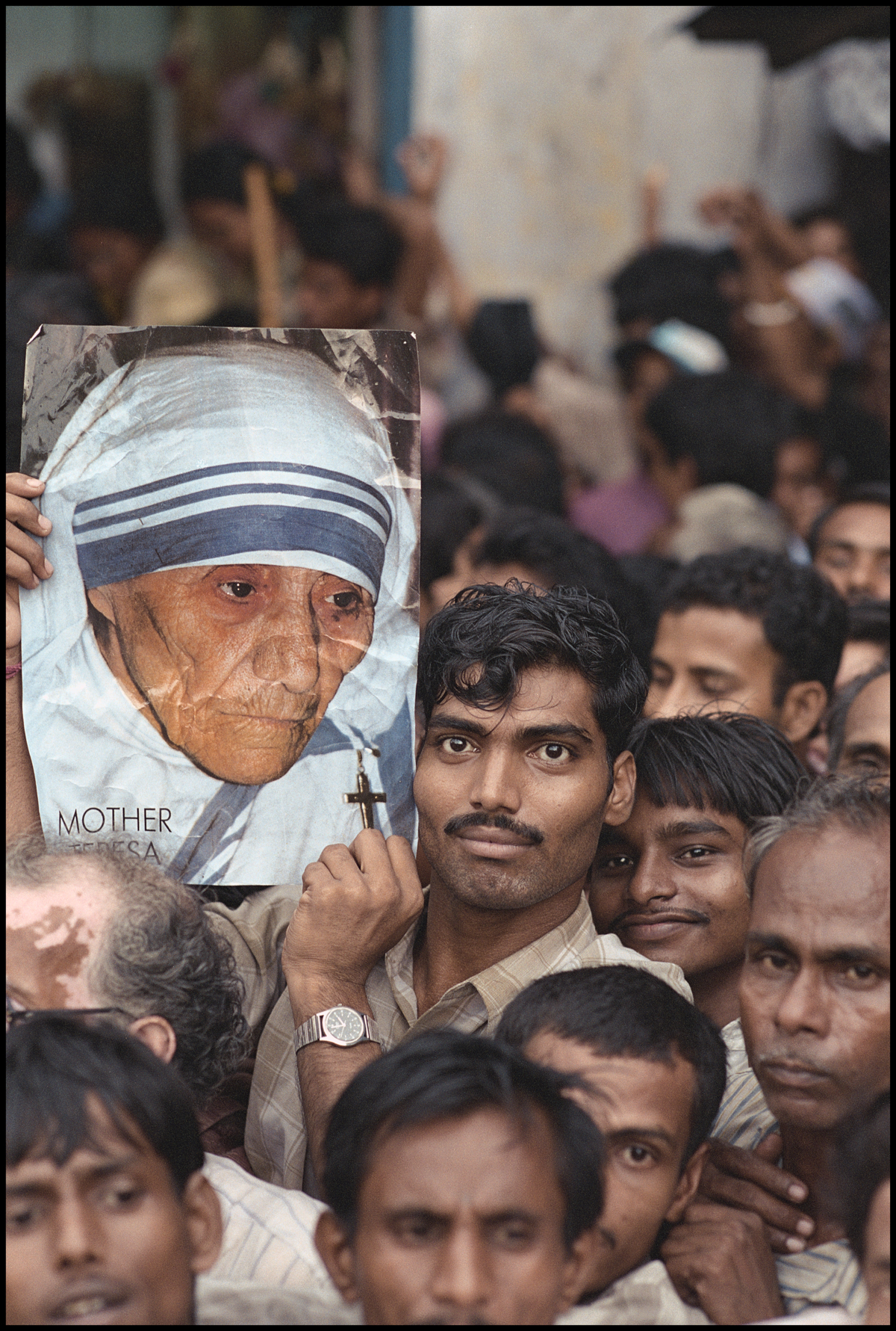 September 1997, Calcutta, India --- Mourner Holding a Picture of Mother Teresa