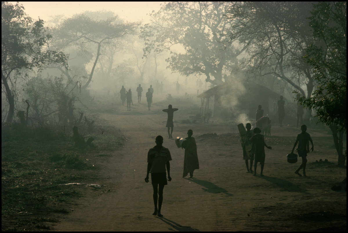 1988, Malawi --- Mozambican refugees walk through smoke and haze along a road in a refugee camp in Malawi.