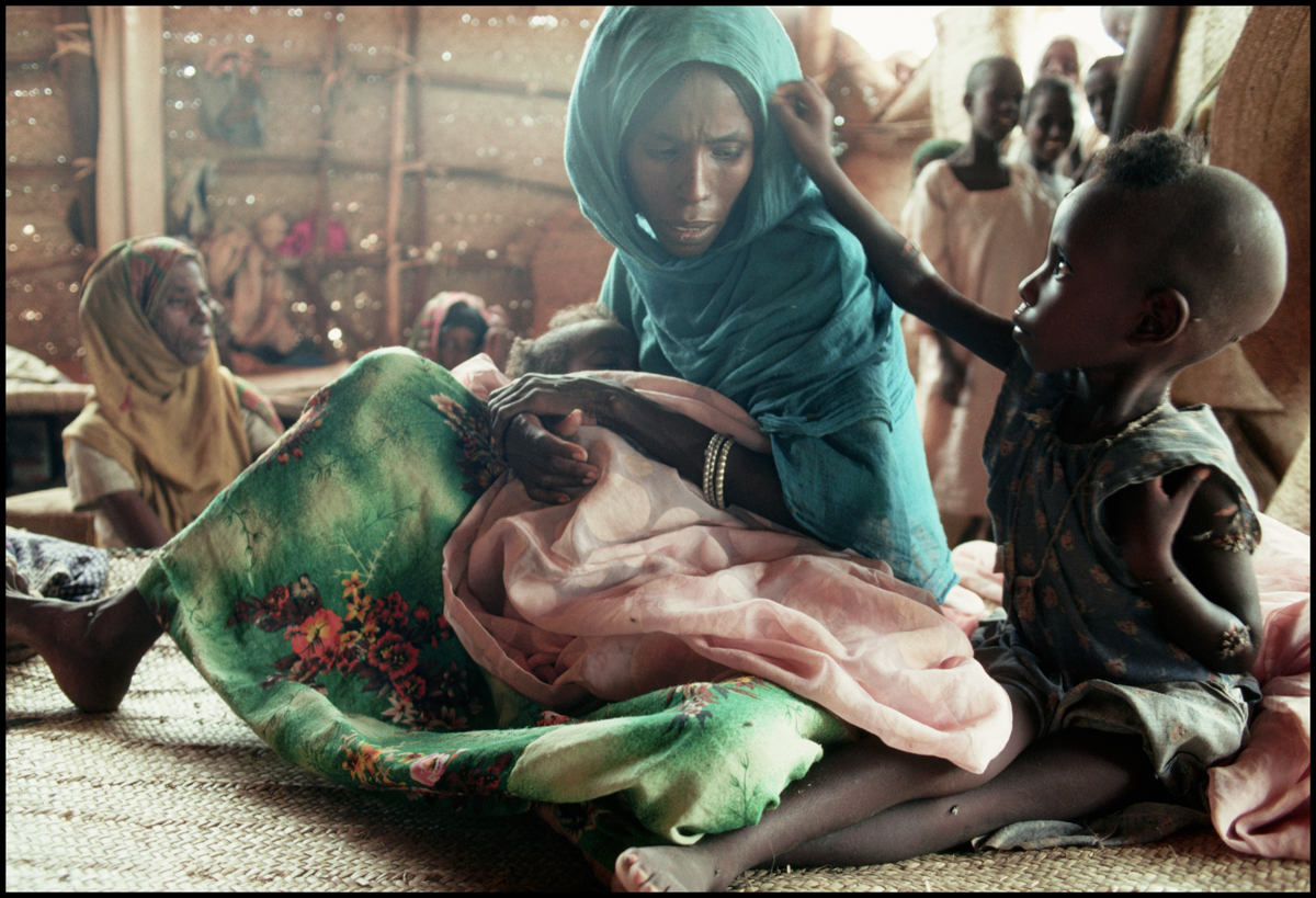 1988, Sudan --- An Ethiopian woman from Eritrea and her starving children sit in a hospital tent located in a refugee camp in eastern Sudan.
