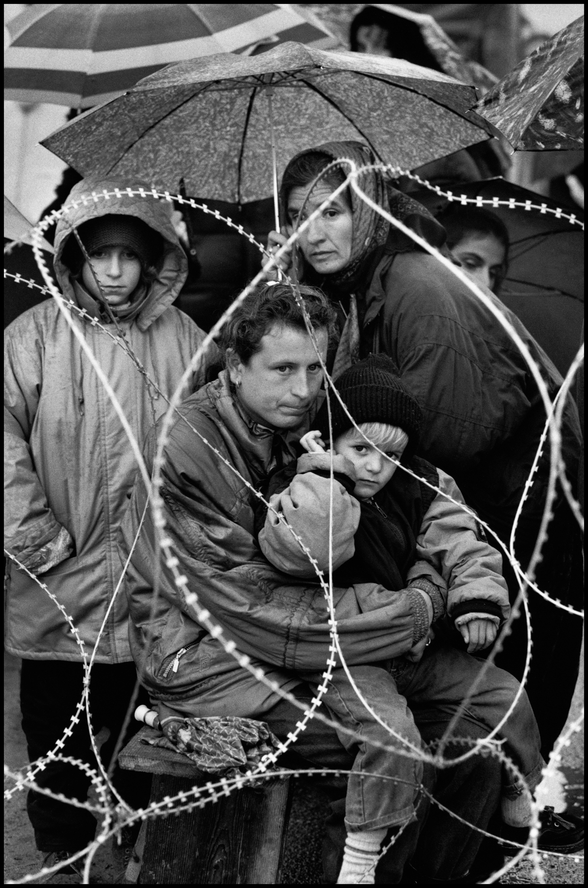 1994, Turanj, Croatia --- A group of pro-Serbian Muslim refugees, probably a family, sit behind barbed wire in a refugee camp in Turanj, Croatia