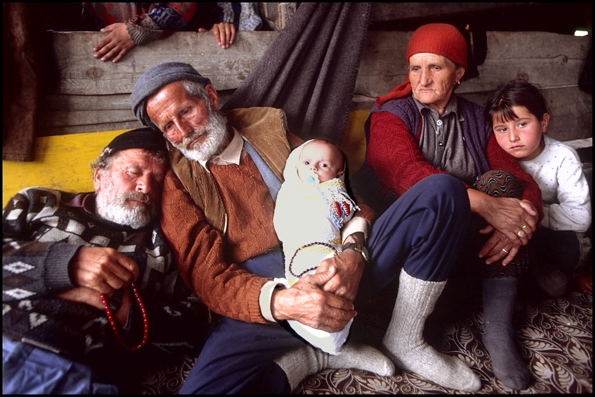 1999, Albania --- Kosovar-Albanian refugees speak to each other across a fence barrier in a refugee camp in Macedonia during the 1999 war in Kosovo.