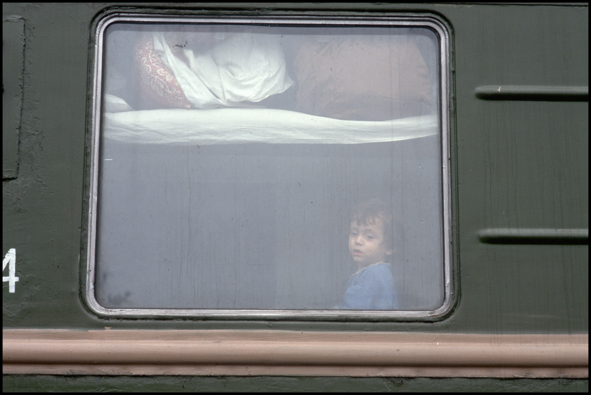 1995, Grozny, Russia --- A Chechen girl looks out her sleeping car window which is her temporary shelter after fleeing the war.